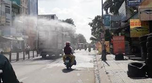 Chủ tiệm rửa xe xịt nước làm mát người đi đường giữa trưa nắng