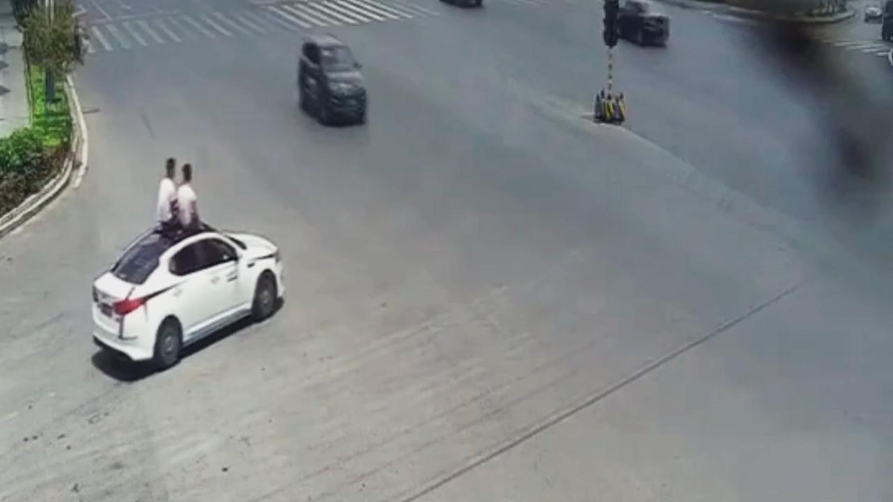 Trời nóng, 2 người đàn ông ngồi trên nóc ô tô 'chạy như bay' để hóng gió