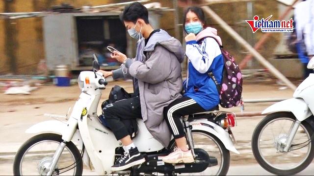 Học sinh đầu không mũ BH, tay lướt điện thoại phóng xe vun vút đến trường