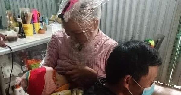 Người đàn ông ngồi xổm, địu con để vợ cho con bú một cách khó khăn, biết được nguyên nhân ai nấy đều xuýt xoa, ngưỡng mộ