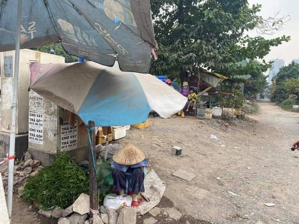 Bức ảnh bà cụ bán rau ngồi bó gối giữa phố Sài Gòn khiến dân mạng cảm động, bất ngờ nhất là hành động của chàng trai chụp hình-1