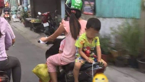 Mẹ để con trai ngồi ngược sau yên xe máy chơi đùa khi đi đường, mặc kệ xe tải chạy sát vách gây phẫn nộ