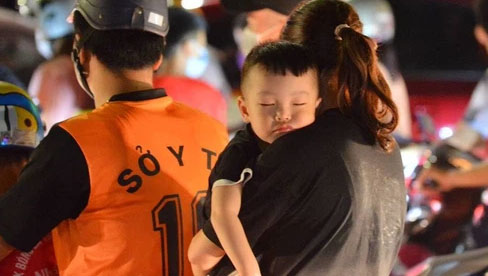 Phụ huynh mệt nhoài, trẻ em ngủ gật trên vòng tay cha mẹ sau khi xem pháo hoa ngày Giỗ Tổ Hùng Vương