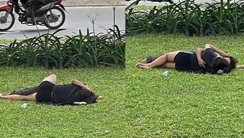 Cặp đôi nằm ôm hôn nhau thắm thiết trên bãi cỏ, mặc kệ xe cộ qua lại xung quanh