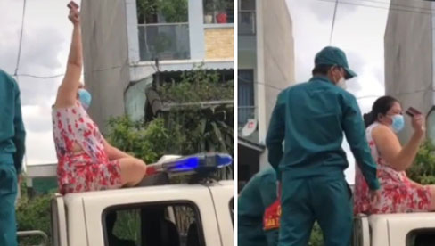 Không đeo khẩu trang, người phụ nữ còn trèo lên nóc xe cảnh sát ngồi, múa may làm loạn nơi công cộng